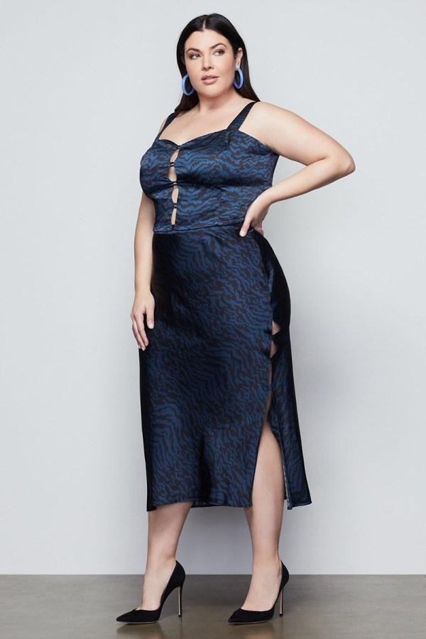A plus-size model wearing a navy zebra print satin slip skirt.