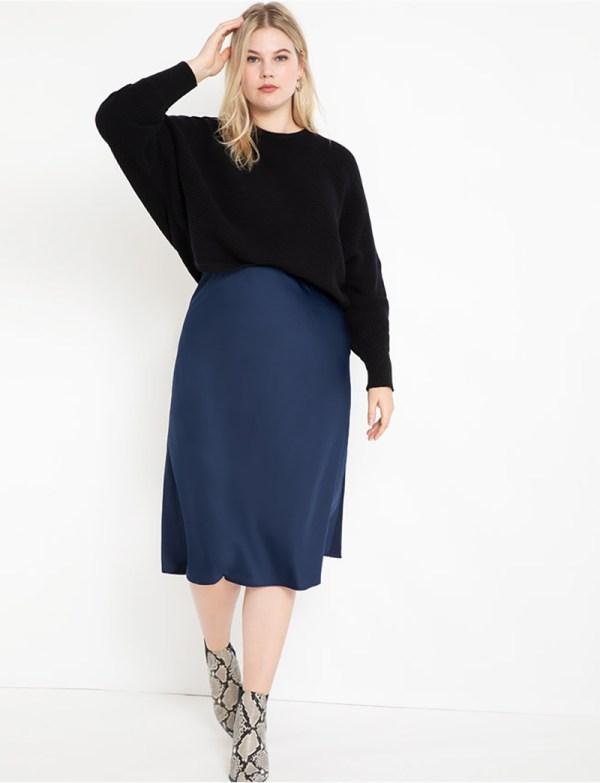 A plus-size model wearing a navy satin slip skirt.
