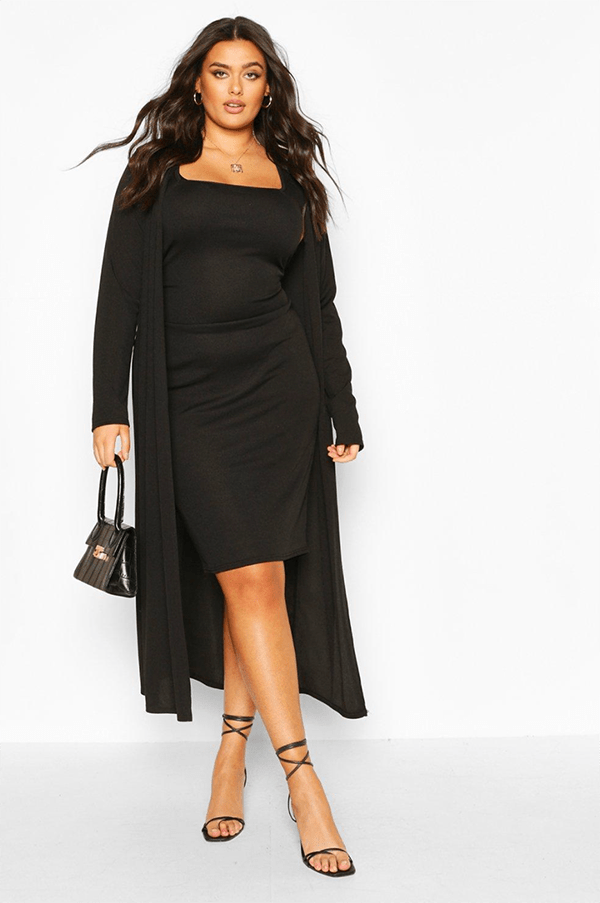 A plus-size model wearing a black midi dress and matching duster.