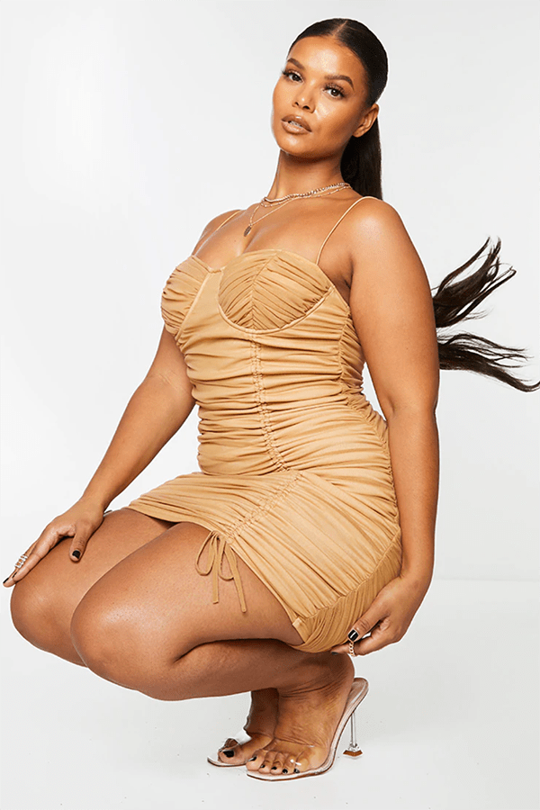 A plus-size model wearing a tan ruched mini dress.