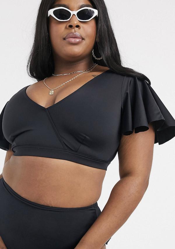 Woman wearing a black bikini with flutter sleeves.