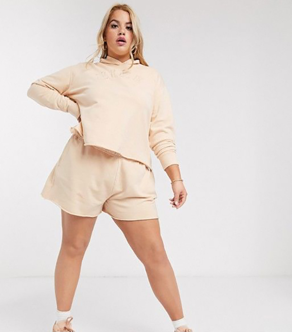 A plus-size model wearing off-white sweat shorts.