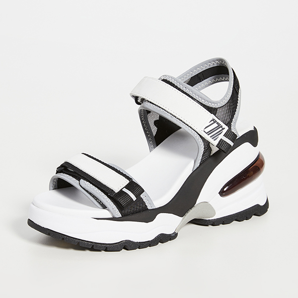 A black and white, velcro-strapped, high-heel sneaker sandal.