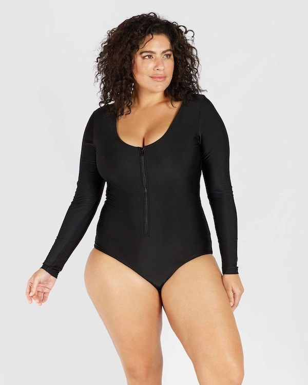 A model wearing a plus-size black swimsuit with sleeves.
