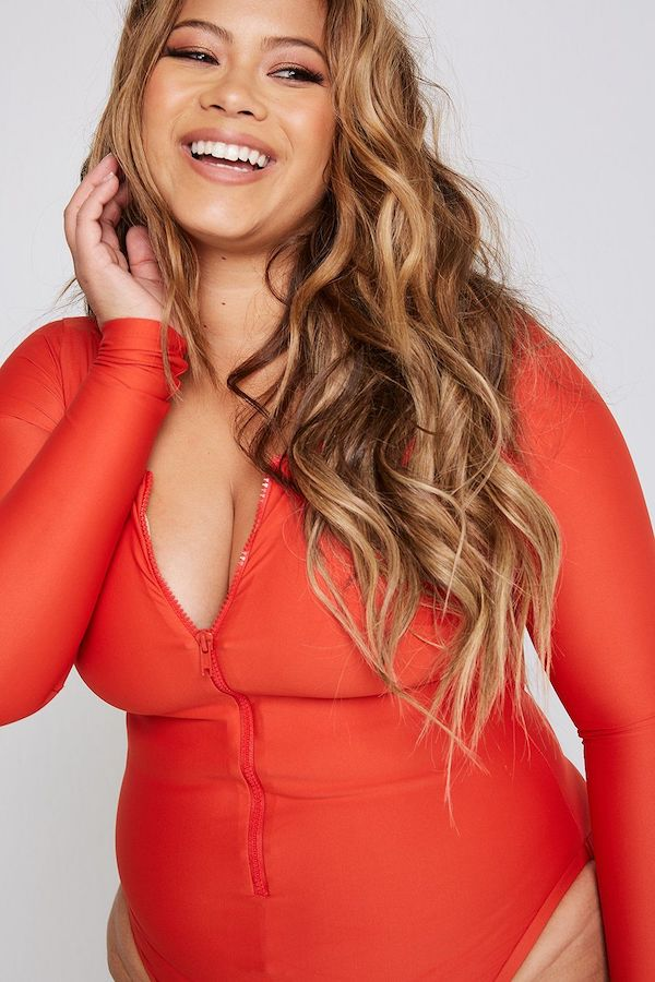 A model wearing a plus-size swimsuit with sleeves in burnt orange.
