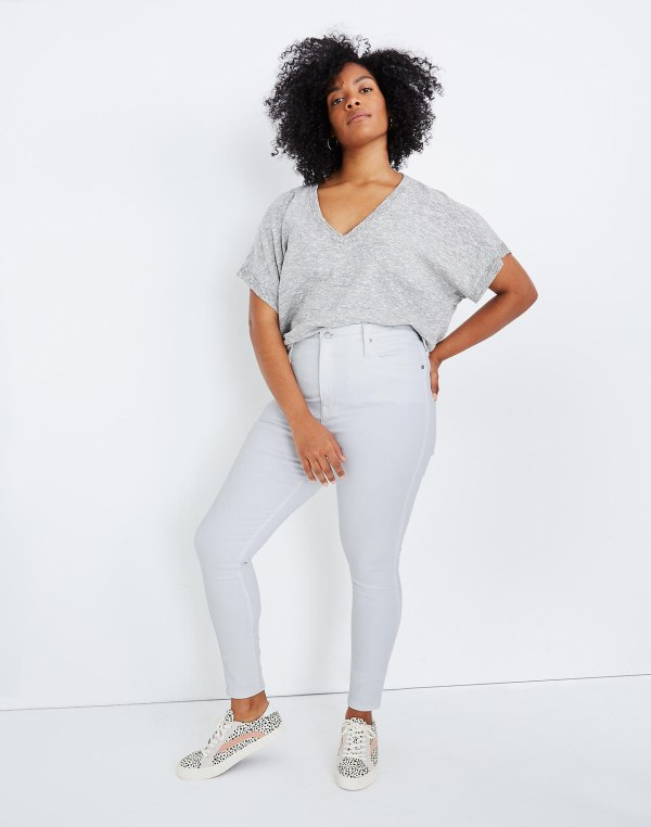 A woman wearing a gray shirt and white jeans.