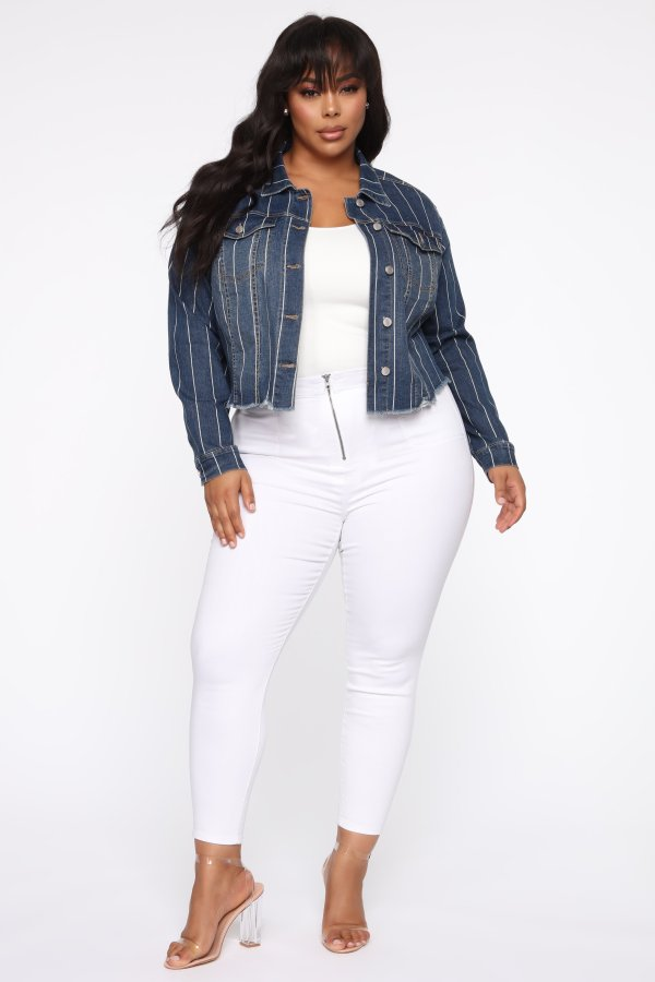 A woman wearing a white top, denim jacket, and white jeans.