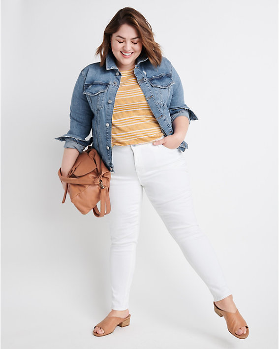 A woman wearing a yellow top, denim jacket, and white jeans.