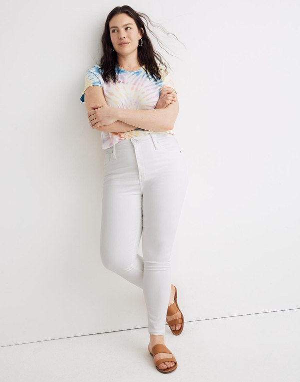 A woman wearing a white shirt and white jeans.