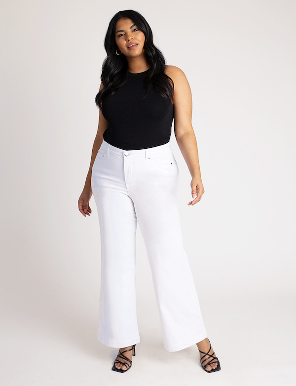 A woman wearing a black tank top and white jeans.