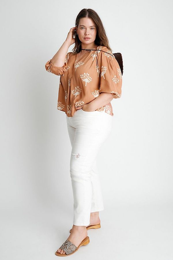 A woman wearing a peach top and white jeans.
