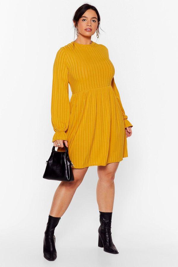 A woman wearing a plus-size mustard dress.
