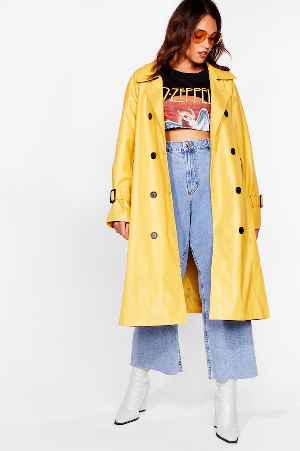 A woman wearing a plus-size yellow trench coat and jeans.