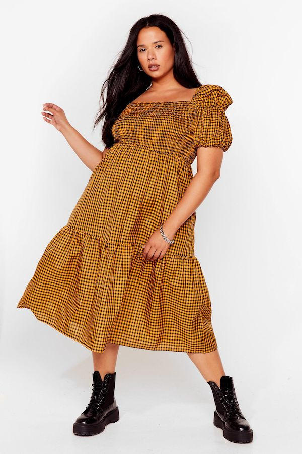 A woman wearing a plus-size brown and black check puff-sleeve dress.