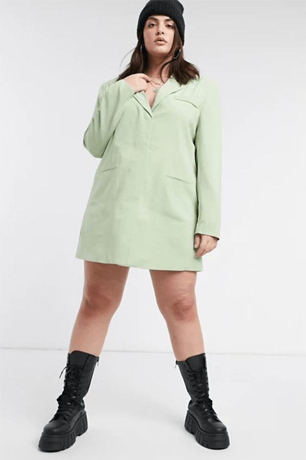 A plus-size model wearing a mint blazer dress.