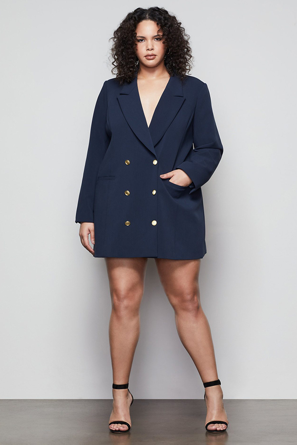 A plus-size model wearing a navy blazer dress.