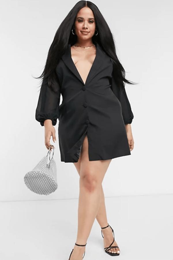 A plus-size model wearing a black blazer dress.