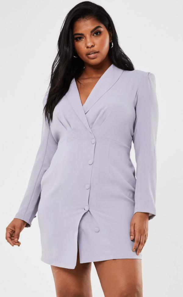 A plus-size model wearing a lavender blazer dress.