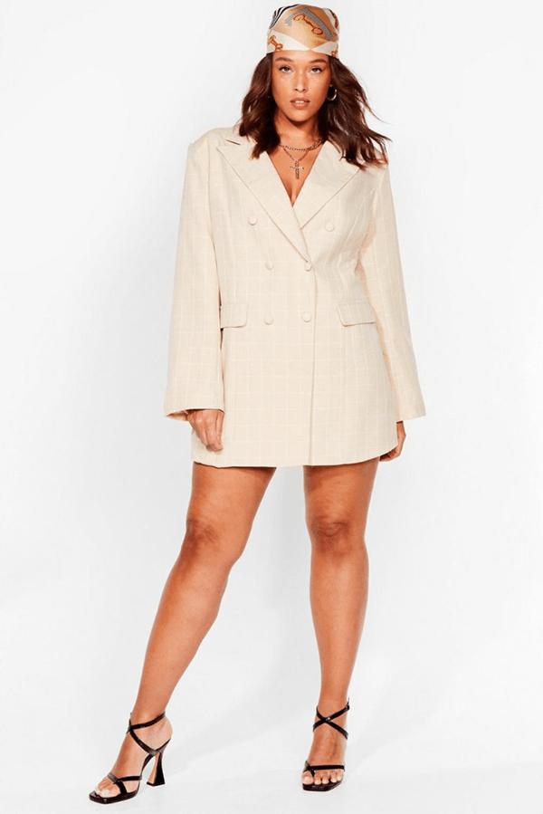 A plus-size model wearing an off-white blazer dress.