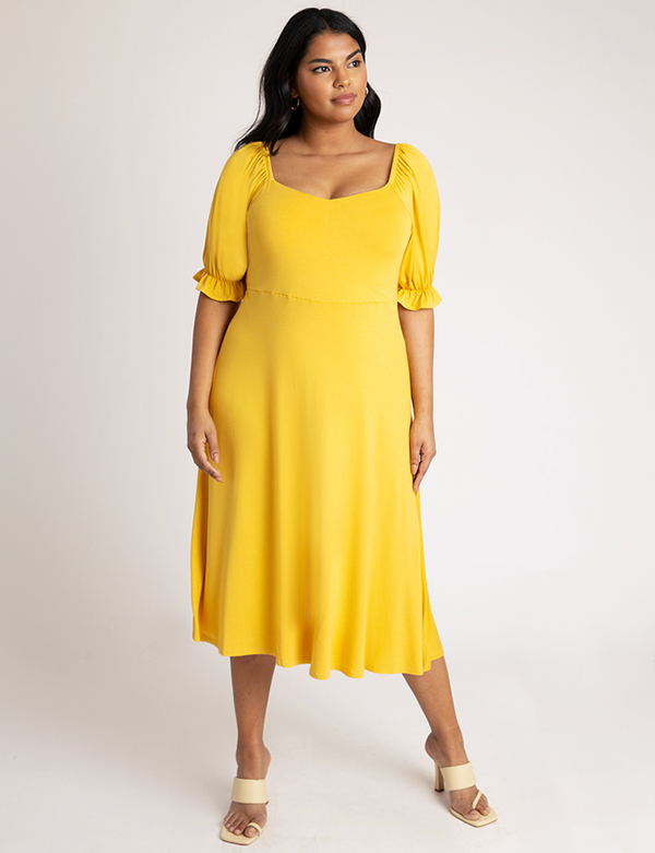 A plus-size model wearing a yellow dress, which is now on sale at Eloquii for less than $29.