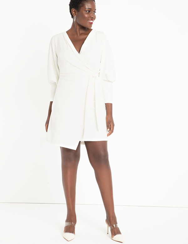 A plus-size model wearing a white wrap dress, which is now on sale at Eloquii for less than $39.