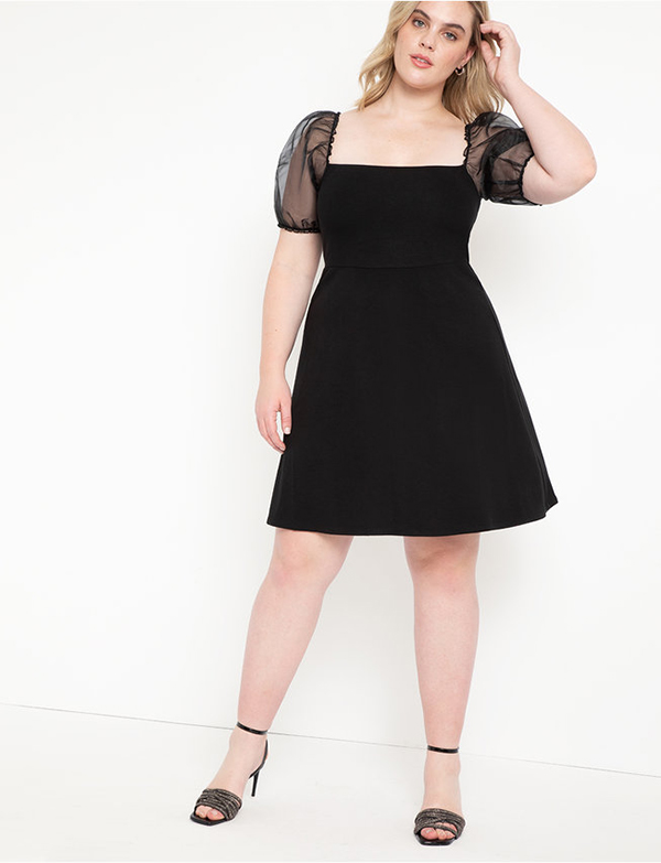 A plus-size model wearing a puff-sleeve black dress, which is now on sale at Eloquii for less than $39.