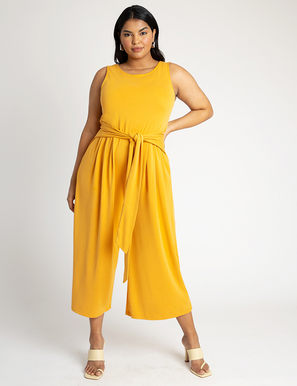A plus-size model wearing a yellow jumpsuit, which is now on sale at Eloquii for less than $49.