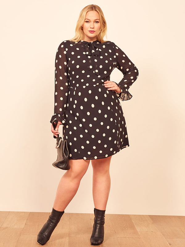 A plus-size model wearing a polka dot mini dress, which are currently on sale at Reformation.