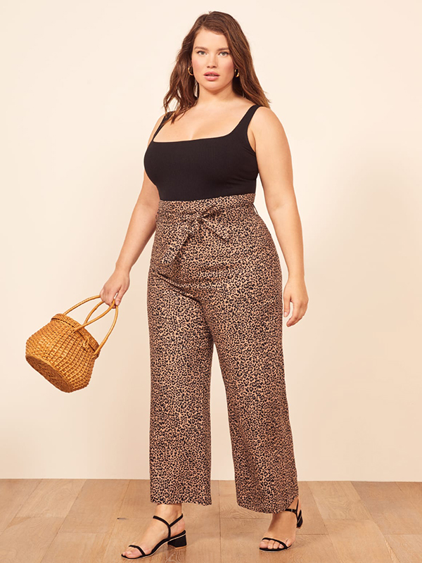 A plus-size model wearing a pair of cheetah print pants, which are currently on sale at Reformation.