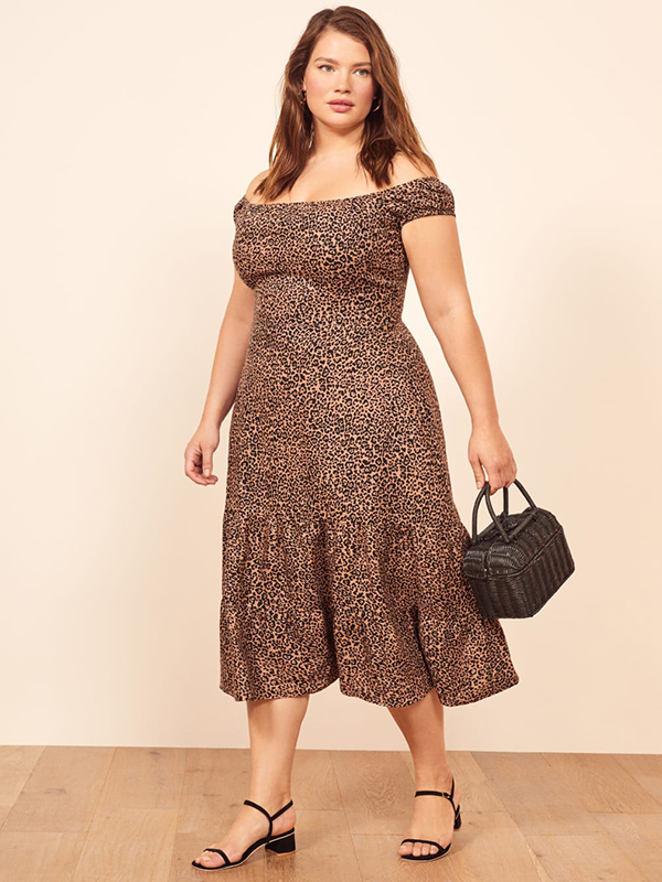 A plus-size model wearing an animal print dress, which are currently on sale at Reformation.