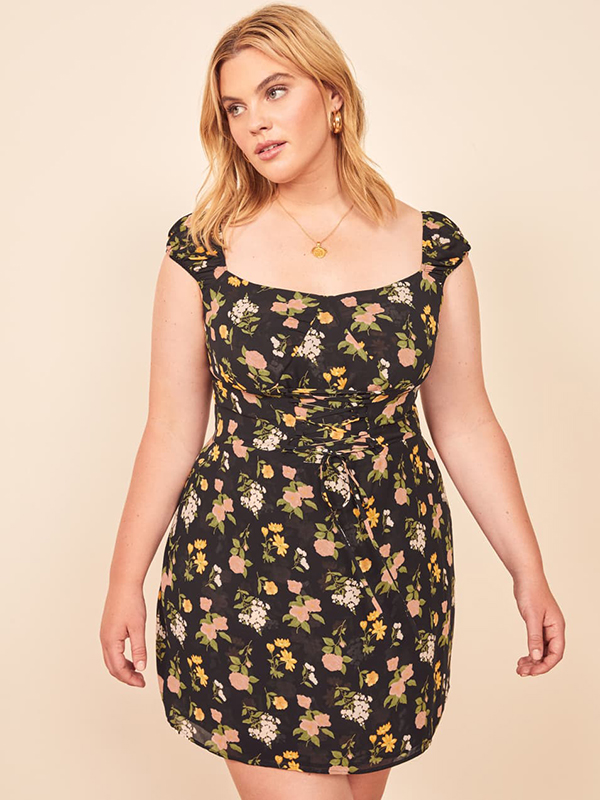 A plus-size model wearing a floral mini dress, which are currently on sale at Reformation.