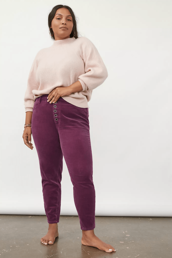 A plus-size model wearing purple corduroy pants.