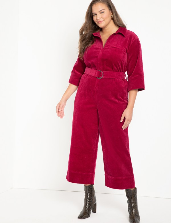A plus-size model wearing a pink corduroy jumpsuit.