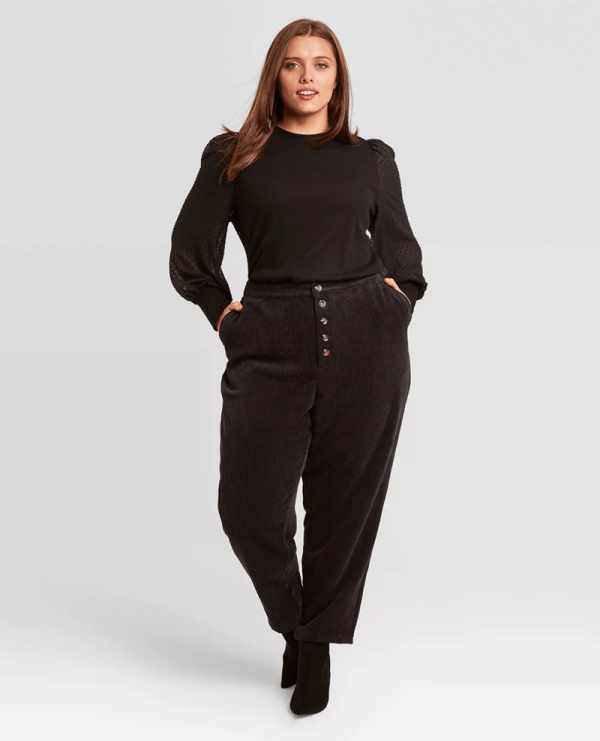 A plus-size model wearing black corduroy pants.