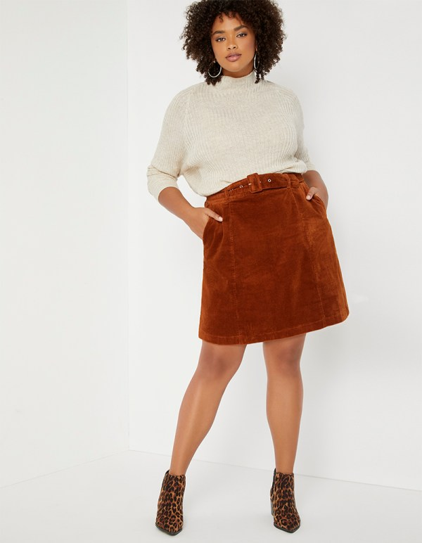 A plus-size model wearing a brown corduroy skirt.
