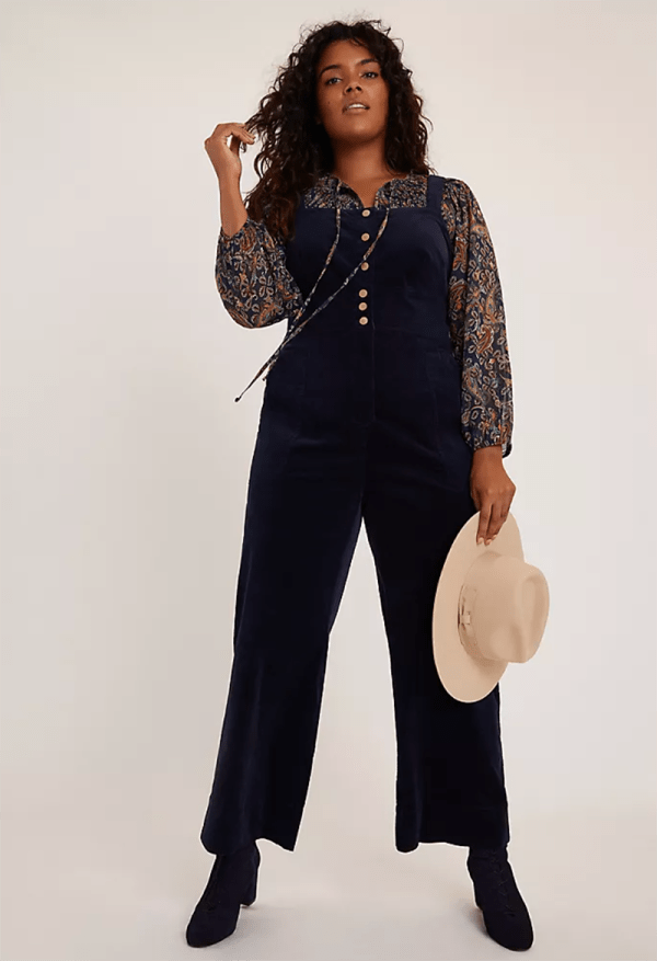 A plus-size model wearing navy corduroy overalls.