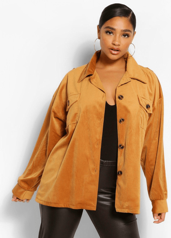 A plus-size model wearing a gold corduroy shacket.