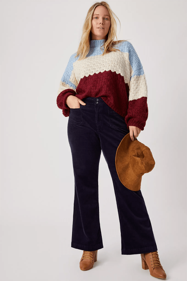 A plus-size model wearing navy corduroy pants.