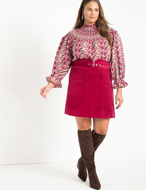 A plus-size model wearing a pink corduroy skirt.