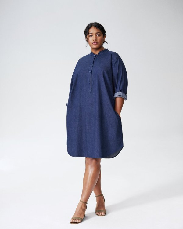 A plus-size model wearing a denim dress.