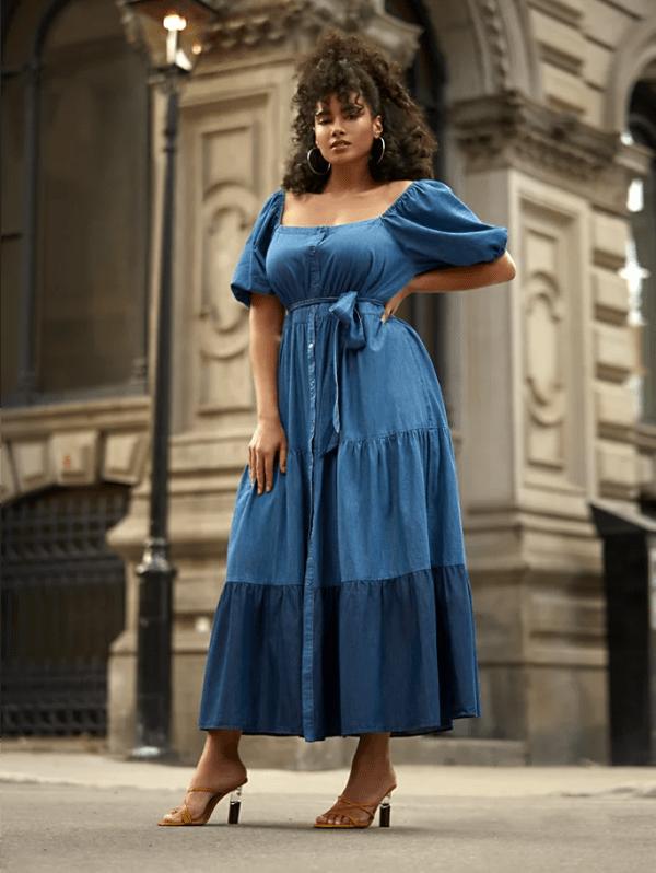 A plus-size model wearing a puff-sleeve denim dress.