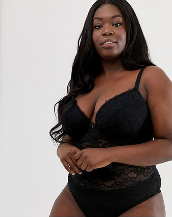A plus-size model wearing a black lingerie bodysuit, which is currently on sale at ASOS.