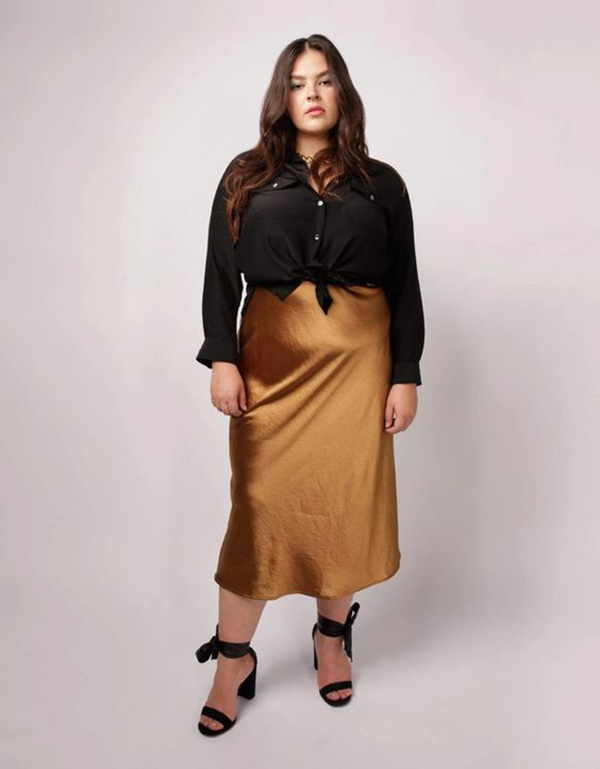 A plus-size model wearing a gold satin midi skirt.