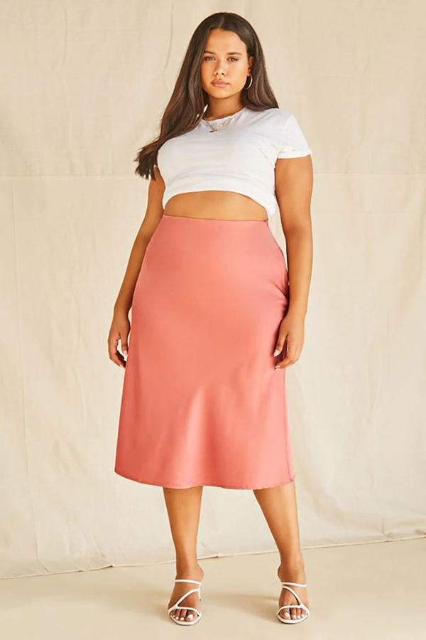 A plus-size model wearing a blush satin midi skirt.
