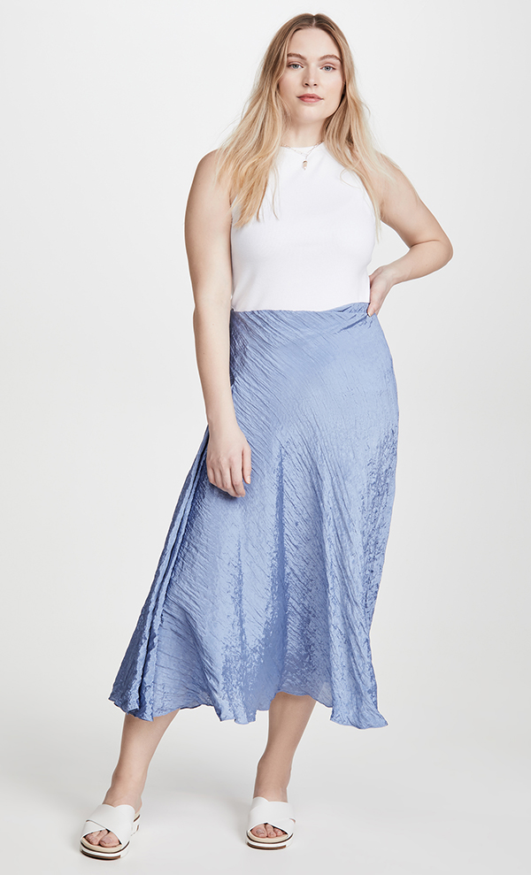 A plus-size model wearing a light blue, satin midi skirt.