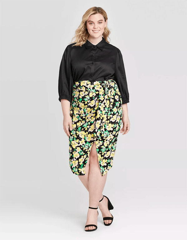 A plus-size model wearing a floral midi skirt.