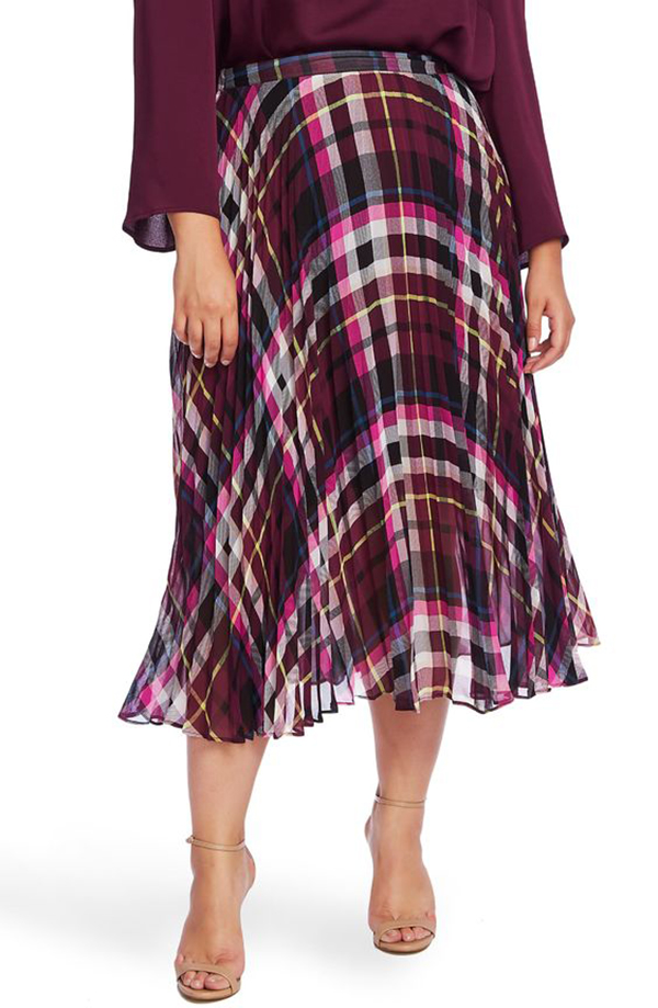 A plus-size model wearing a maroon plaid midi skirt.