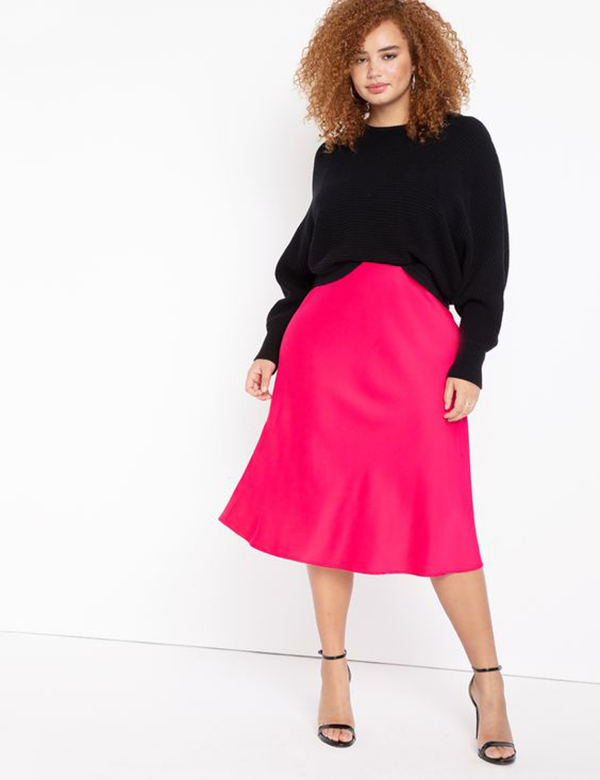 A plus-size model wearing a hot pink satin midi skirt.