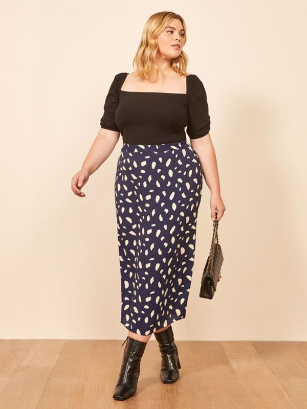 A plus-size model wearing a blue printed midi skirt.