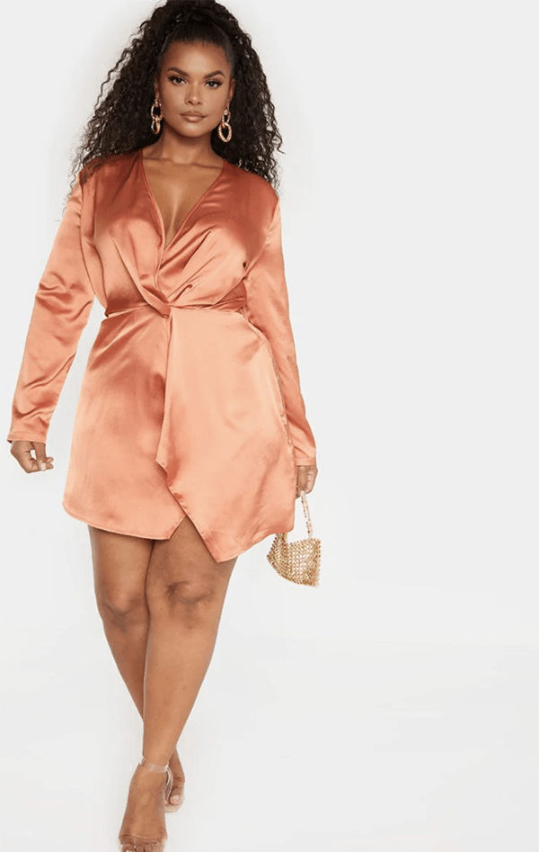 A plus-size model wearing a coral satin mini dress.